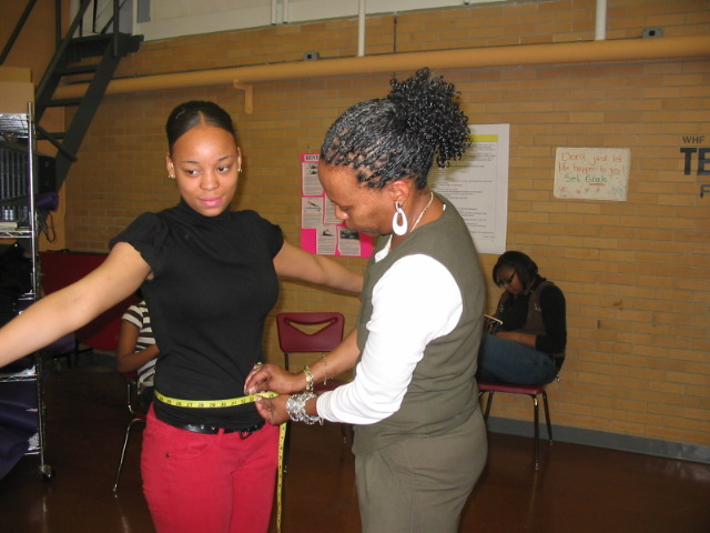 picture of Trenton Central High School student in the WHF Teen Esteem program having her waist measured by her PE Teach Ms. Kelley